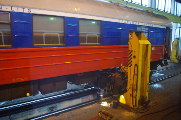 "At the Russian border, the train is broken into two four-car sections, run into a large shed, and spotted so that each rail car is precisely positioned between four hydraulic jacks, one at each corner. The wheel assemblies (we call them ""trucks""; they're called ""bogies"" in Europe) are detached, then the jacks lift each rail car a couple of feet in the air."