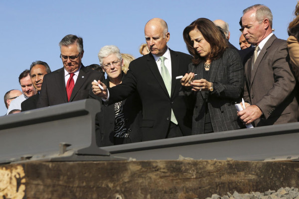 California Governor Jerry Brown (C) and his wife, Anne Gust, prepare to sign a railroad rail during a ceremony for the California High Speed Rail in Fresno, Calif., on Jan. 6, 2015. Photo by Robert Galbraith/Reuters
