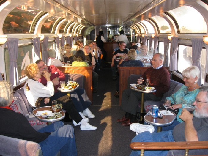 The Pacific Parlour Car includes overstuffed, swiveling easy chairs, a lounge area, booths for dining, and a bar with an attendant.